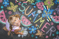 Child drawing summer spirit on asphalt Royalty Free Stock Photo