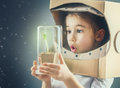 Child is dressed in an astronaut costume sees a sprout a glass case the concept of environmental protection Stock Photos