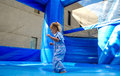 A child dressed in blue plays in a blue bouncy house at a fair Royalty Free Stock Photos