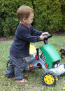 Child driving toy tractor toddler a in a garden Royalty Free Stock Image