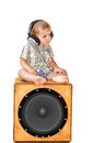 Child in earpiecess sitting on subwoofer Royalty Free Stock Photography