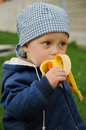 Child eating banana little a delicious fresch Stock Images