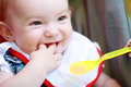 Child eating eat smeared pretty baby girl from spoon outdoor Royalty Free Stock Images