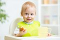 Child Eating Food In Highchair