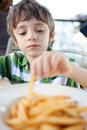 Child eating french fries Royalty Free Stock Images