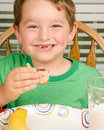 Child eating messy peanut butter and jelly sandwich with milk fruit for healthy lunch Royalty Free Stock Photo