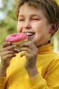 Child eating a pink doughnut Stock Photo