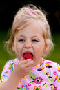 Child eating a strawberry in the garden Royalty Free Stock Photo