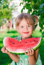 Child eating watermelon on the park in summer time. . Enjoy. Portrait.  Happy girl. Royalty Free Stock Photo