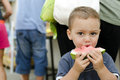 Child eating watermelon on a street or market Royalty Free Stock Image