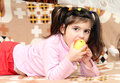 Child eats an apple lying Stock Images