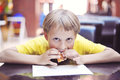 Child eats in a cafe cakes over the table Royalty Free Stock Photography