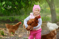 image photo : Child enjoying holding chicken in her arms.