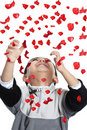 Child Enjoying a Shower of Red Rose Petals Royalty Free Stock Photo