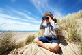 Child explorer at the beach little boy searching with binoculars dressed as concept for nature discovery exploring and education Stock Images