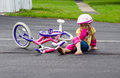 Child falling off a bike little girl in safety gear sits in the middle of drive after her new Royalty Free Stock Images