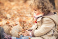 Child feeds a little squirrel happy in autumn park Royalty Free Stock Photography