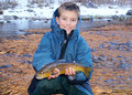 Child fishing holding a large trout boy in the winter smiling and big sized brown and his fly rod or pole and reel Stock Photo