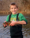 Child fishing holding a rainbow trout boy in stream smiling and Stock Photography
