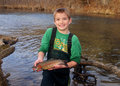Child fishing holding a rainbow trout boy in stream smiling and Stock Images