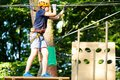 Child in forest adventure park. Kid in orange helmet and blue t shirt climbs on high rope trail. Agility skills and climbing Royalty Free Stock Photo