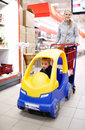 Child friendly supermarket shopping with a young mother pushing her small son in a colourful plastic car attached to the Stock Photos