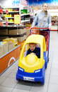 Child friendly supermarket shopping with a young mother pushing her small son in a colourful plastic car attached to the Stock Images