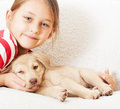 Child gently hugs puppy little blue eyed girl tenderly embraces the Stock Images