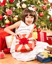 Child with gift box near Christmas tree. Royalty Free Stock Photo