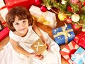 Child with gift box near Christmas tree. Royalty Free Stock Photography