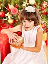 Child with gift box near Christmas tree. Stock Photo