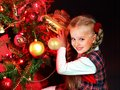 Child with gift box near christmas tree glowing lights Royalty Free Stock Photos
