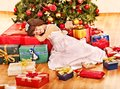 Child with gift box near christmas tree sleeping Stock Photos