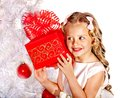 Child with gift box near white christmas tree isolated Royalty Free Stock Photos