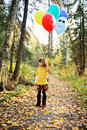 Child girl with balloons in autumn forest Royalty Free Stock Photography