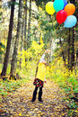 Child girl with balloons in autumn forest Royalty Free Stock Photo