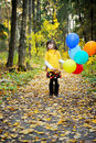 Child girl with balloons in autumn forest Royalty Free Stock Images