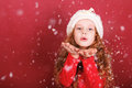 Child girl blowing snow with her hand. Royalty Free Stock Photo