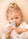 Child girl with bottle with infant formula at home the concept of food and parenting Royalty Free Stock Photography