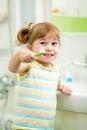 Child girl brushing teeth in bathroom Royalty Free Stock Photo