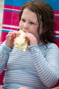 Child girl with cheese hoagie sandwhich on a deck chair by the ocean Royalty Free Stock Photo