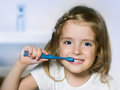 Child girl cleaning teeth with toothbrush in the bathroom Royalty Free Stock Images