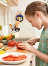 Child girl cooking in home kitchen, chopping tomatoes. Basket of vegetables and fresh fruits in kitchen interior. Healthy food con