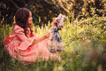 Child girl dressed as fairytale princess playing with doll in summer forest