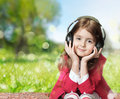 Child girl earphones outdoor empty space background listen to music learn foreign language audio study sitting on green grass Royalty Free Stock Photography