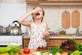 Child girl eat cherries, fruits and vegetables in home kitchen i