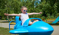 Child girl fly on blue airplane attraction in city park, happy childhood, summer vacation concept Royalty Free Stock Photo