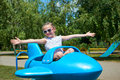 Child girl fly on blue plane attraction in city park, happy childhood, summer vacation concept Royalty Free Stock Photo