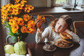 Child girl having breakfast at home in autumn morning. Real life cozy modern interior in country house Royalty Free Stock Photo