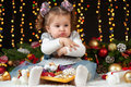 Child girl hides her toys, portrait in christmas decoration, winter holiday concept, dark background with illumination and boke li Royalty Free Stock Photo